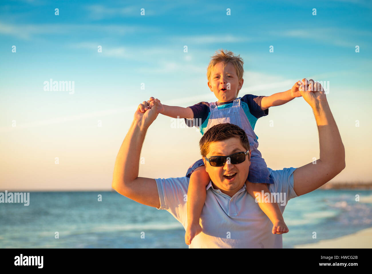 Father giving his son piggyback ride on beach - Stock Image