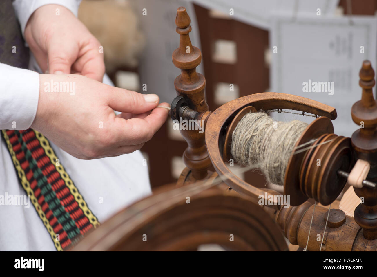 Hands of woman spinning line flax with a spinning wheel Stock Photo