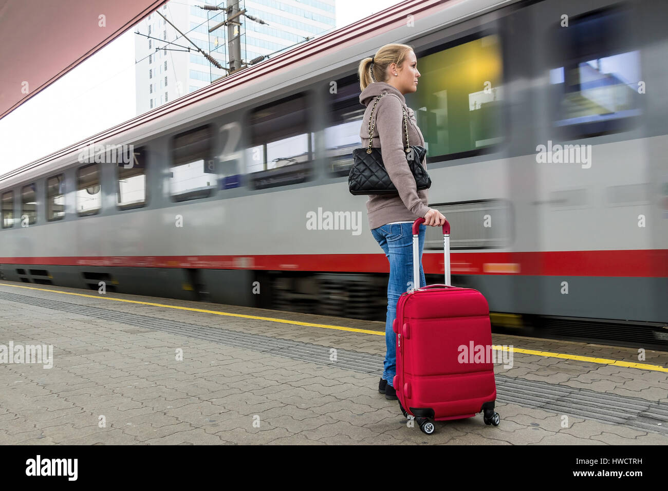 A young woman waits for a train in a railway station. Train journey in the vacation, Eine junge Frau wartet auf Stock Photo