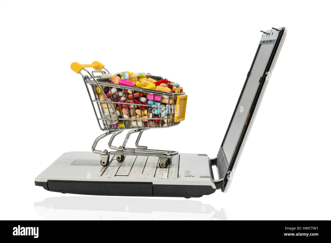 Tablets by shopping cart and computer. Symbolic photo for the purchase of drugs on the Internet, Tabletten mit Einkaufswagen - Stock Image