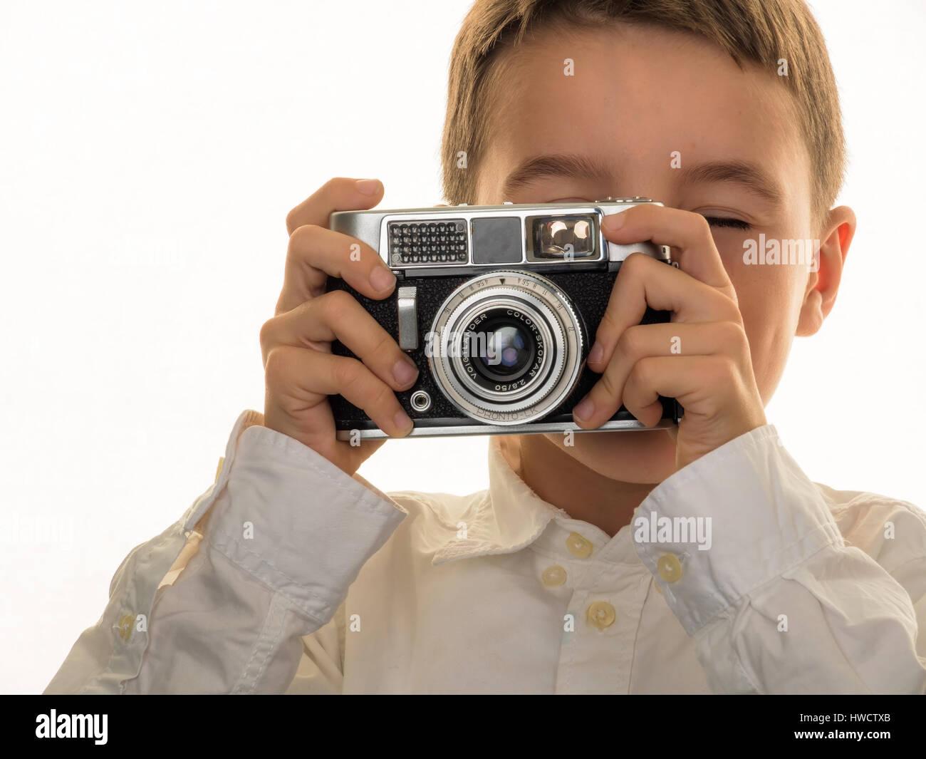 A boy takes photos with an old camera., Ein Junge fotografiert mit einem alten Fotoapparat. Stock Photo