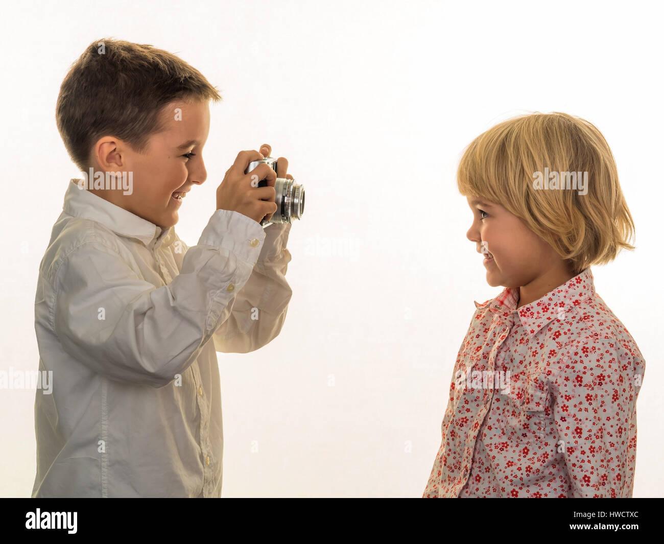 Two children take photos with an old camera., Zwei Kinder fotografieren mit einem alten Fotoapparat. - Stock Image