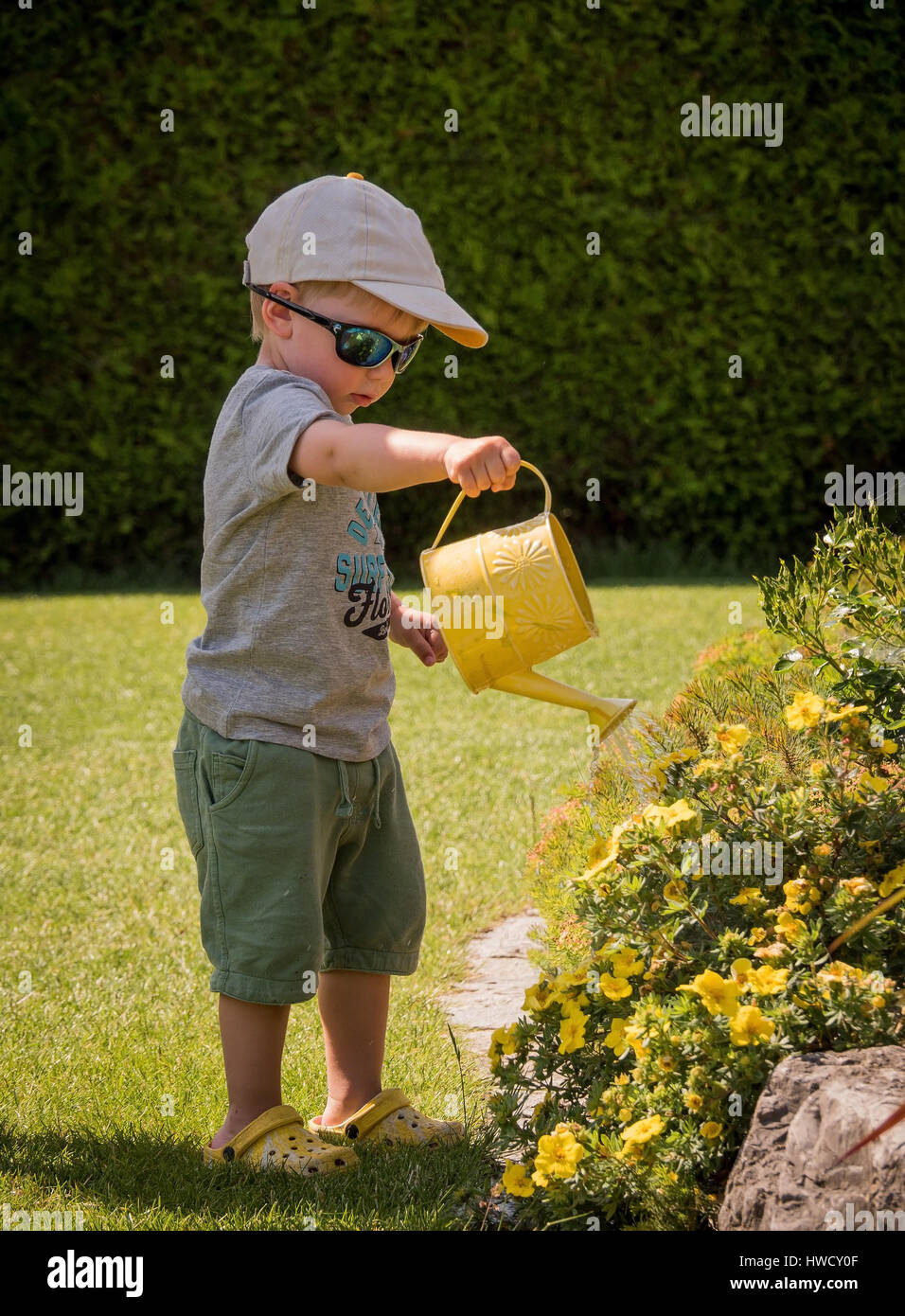 A small boy squirts the flowers on a hot day in summer with a watering can, Ein kleiner Bub spritzt mit einer Gießkanne - Stock Image