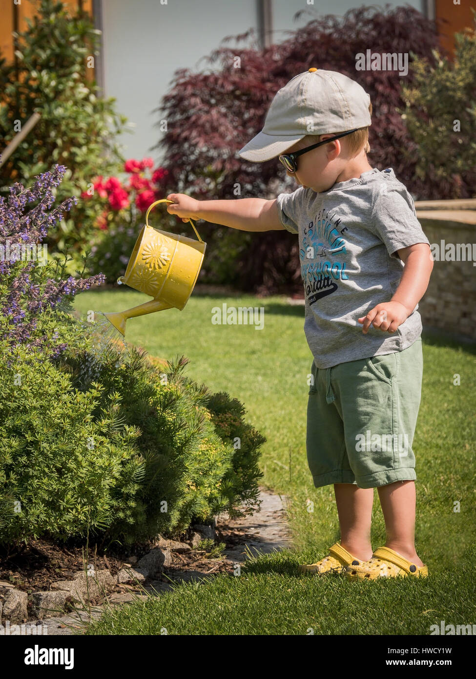 A small boy squirts the flowers on a hot day in summer with a watering can, Ein kleiner Bub spritzt mit einer Gießkanne Stock Photo