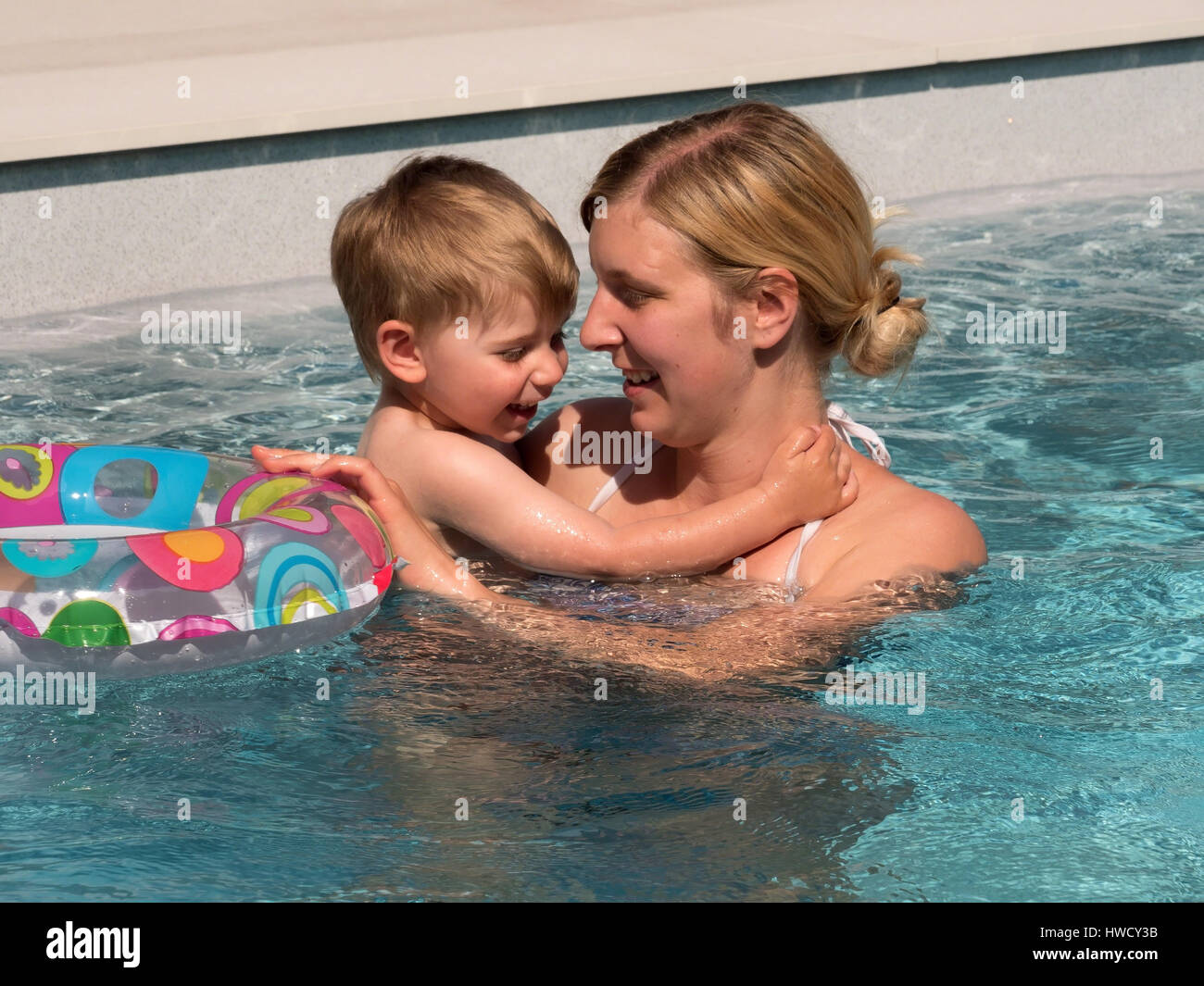 A child swims with a Schwimmreifwn in the pool and cools off on a hot summer day., Ein Kind schwimmt mit einem Schwimmreifwn Stock Photo