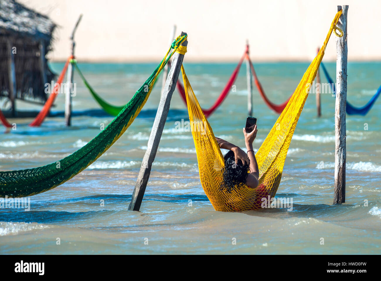 Jericoacoara, Brazil - July 17, 2016: Woman relaxing on hammock and do selfie on vacation - Stock Image