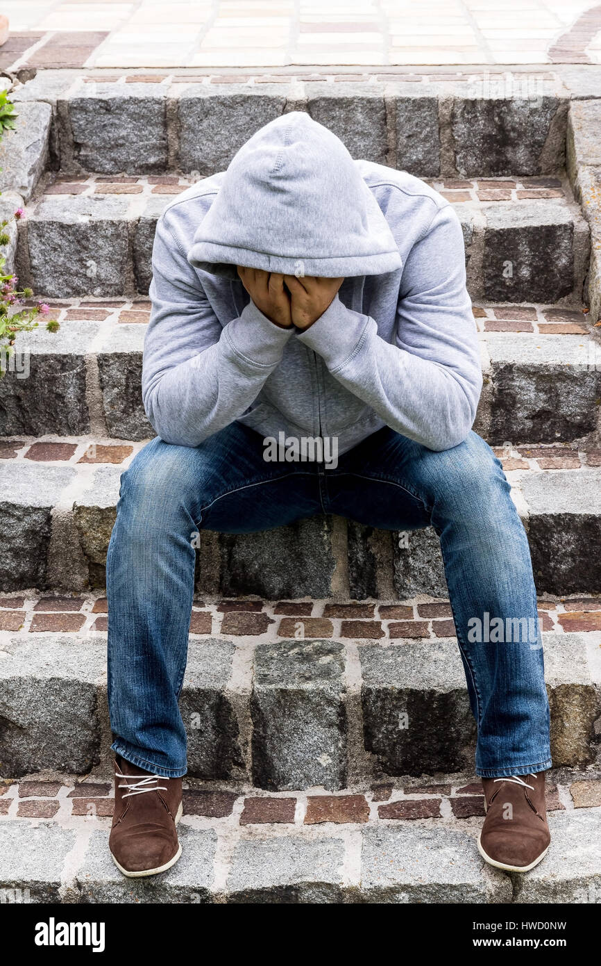 A man sits lonely on steps, Ein Mann sitzt einsam auf Stufen - Stock Image
