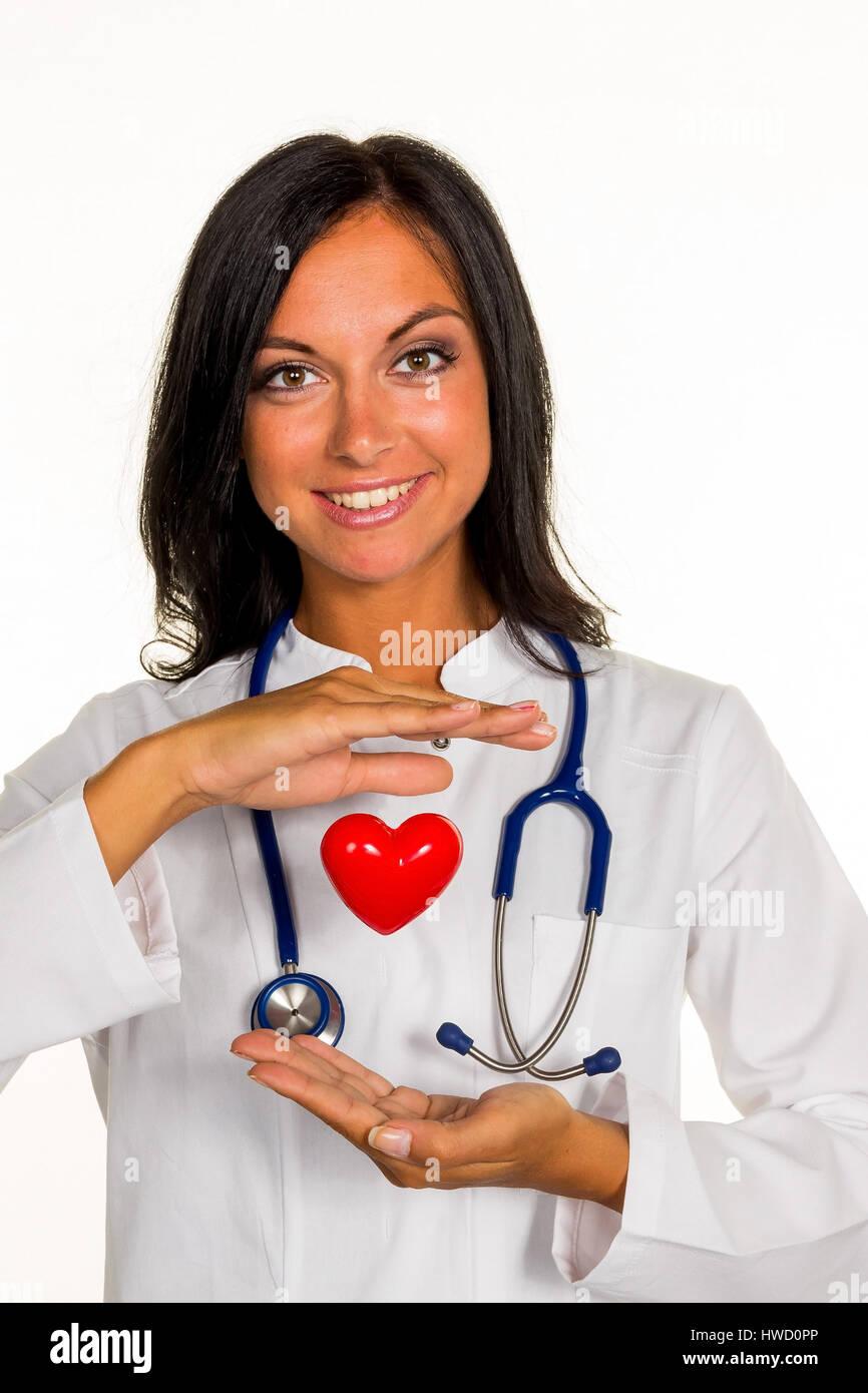 A young doctor internist holds a heart symbolically in the hand., Eine junge ƒrztin (Internistin) h‰lt ein Herz - Stock Image