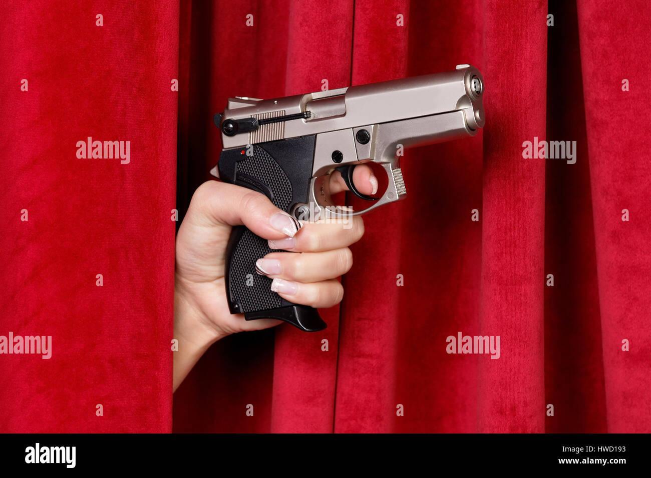 A revolver is pushed by a women's hand by a red curtain, Eine Revolver wird von einer Frauenhand durch einen roten Vorhang geschoben Stock Photo