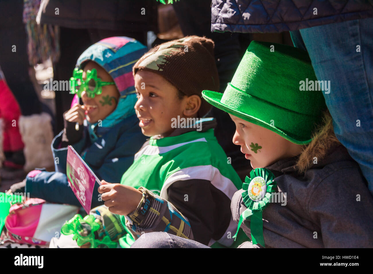 Montreal, Canada - 19 March 2017: 3 kids looking at Montreal's St. Patrick's Day parade - Stock Image