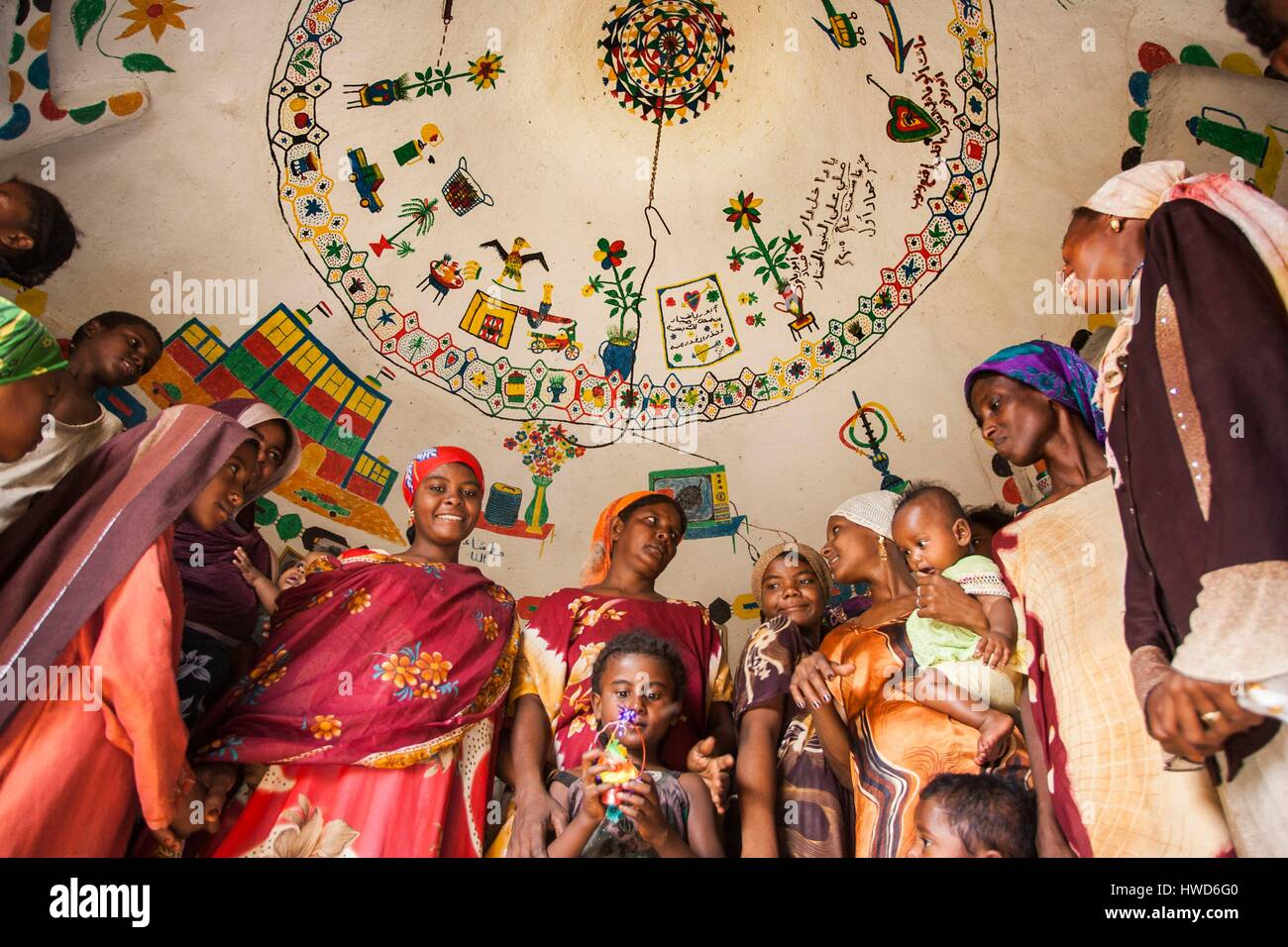 Yemen, Tihama, inside a hut in earth decorated with naive paintings and plates. The women came to watch the shot - Stock Image