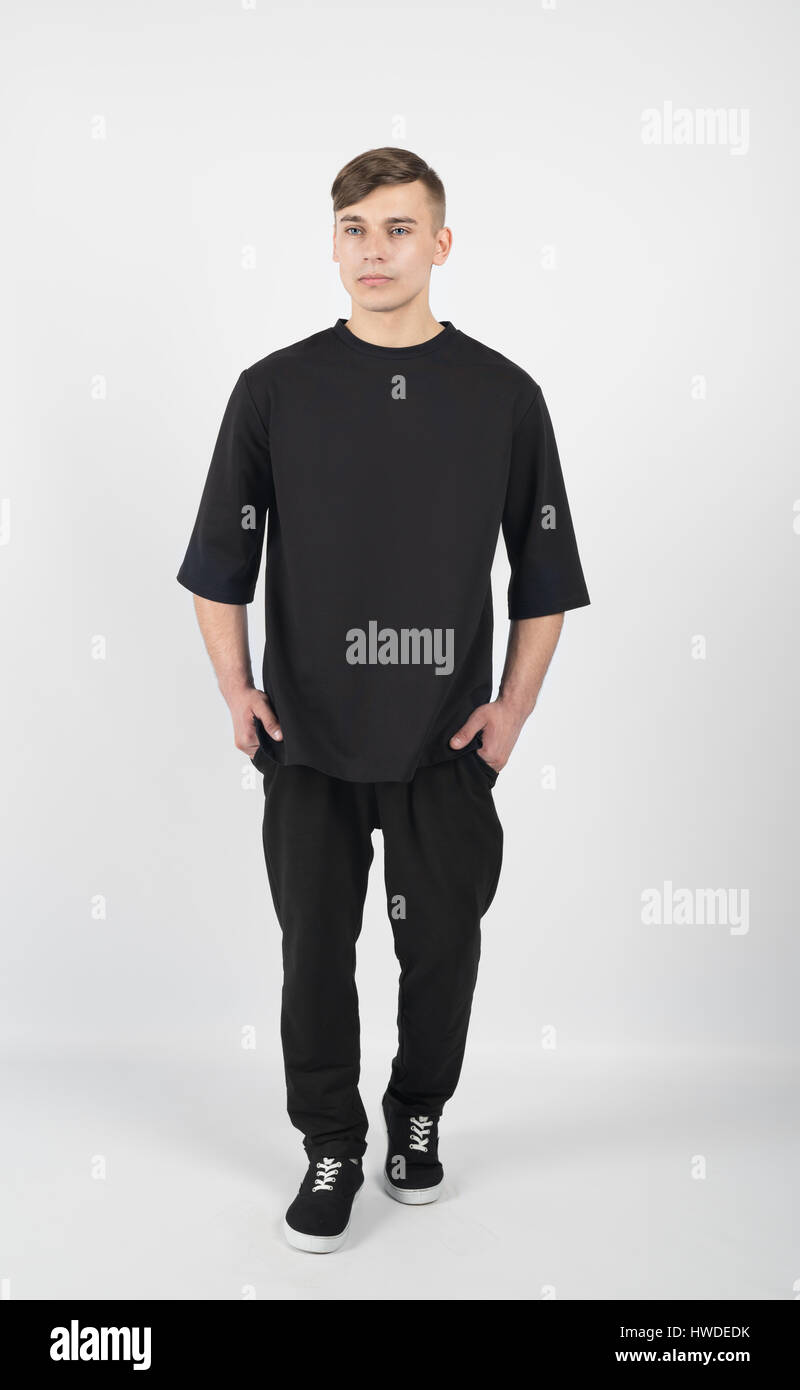 f8fc0fe3 Young muscular guy wearing black clothes and sneakers isolated on white  background
