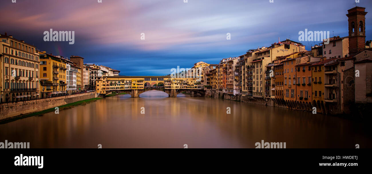 Long exposure panorama of Florence's iconic Ponte Vecchio with a rainbow to the left of it - Stock Image