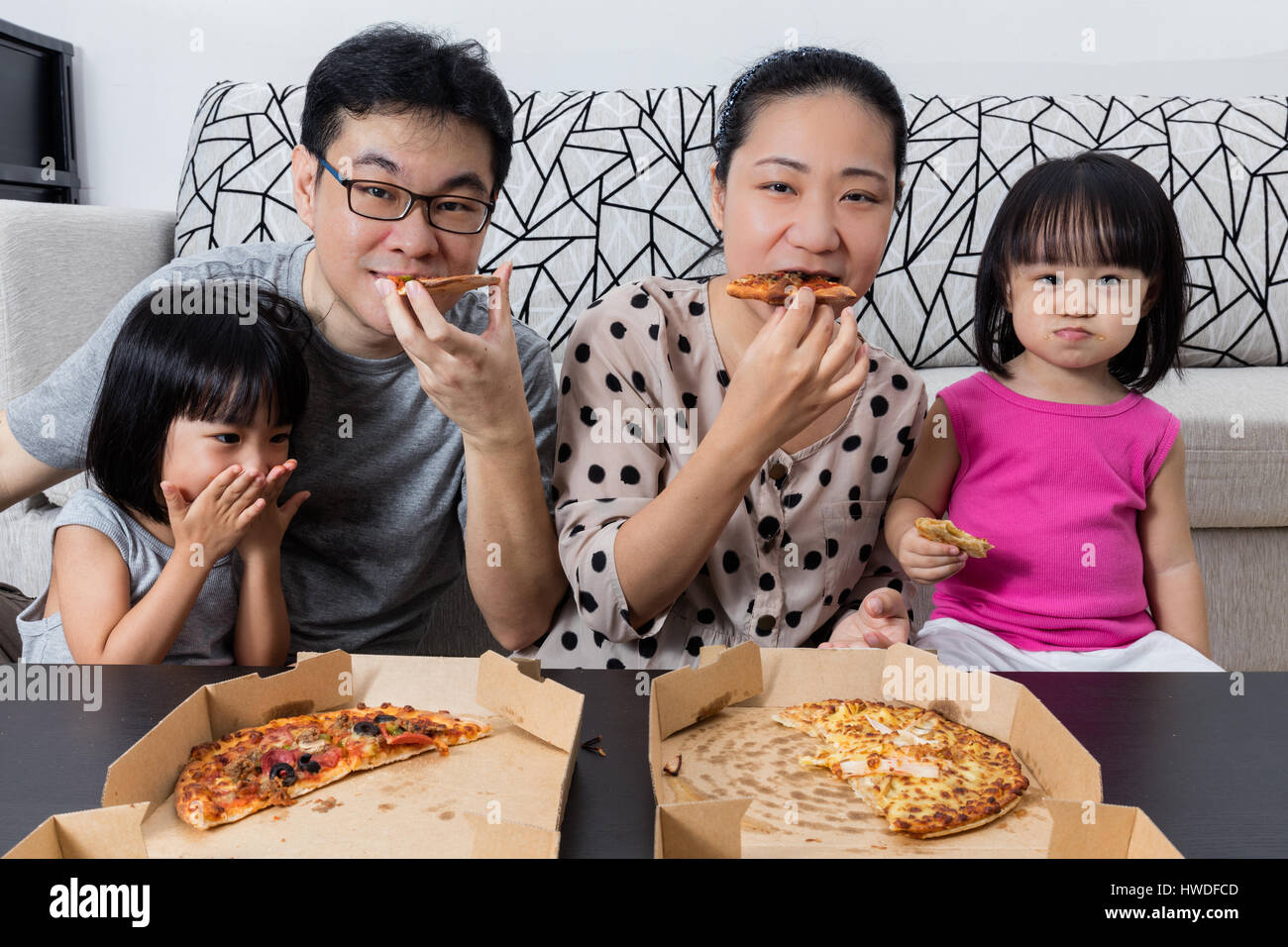 Happy Asian Chinese Family Eating Pizza Together at Home ...