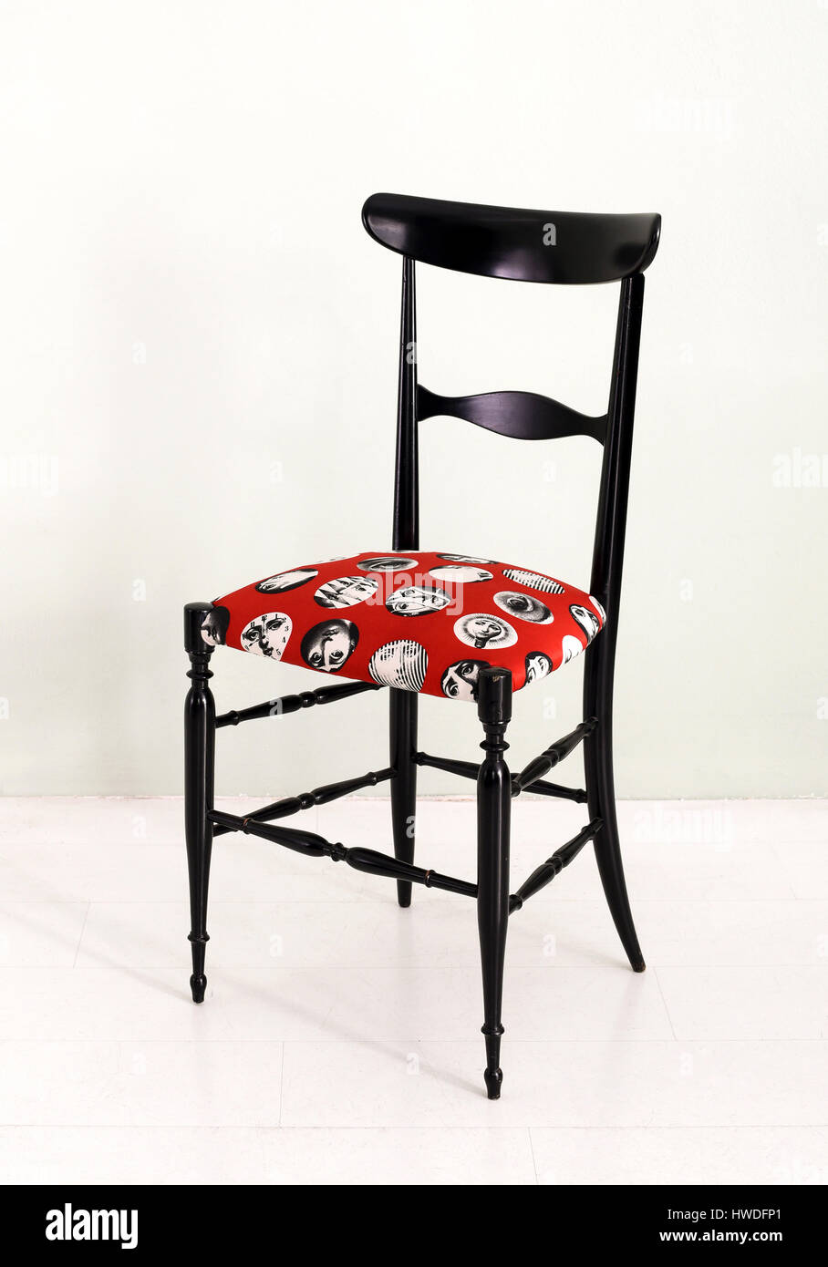 Elegant black Italian designer Fornasetti chair with a bold patterned red upholstered seat and stylish frame - Stock Image
