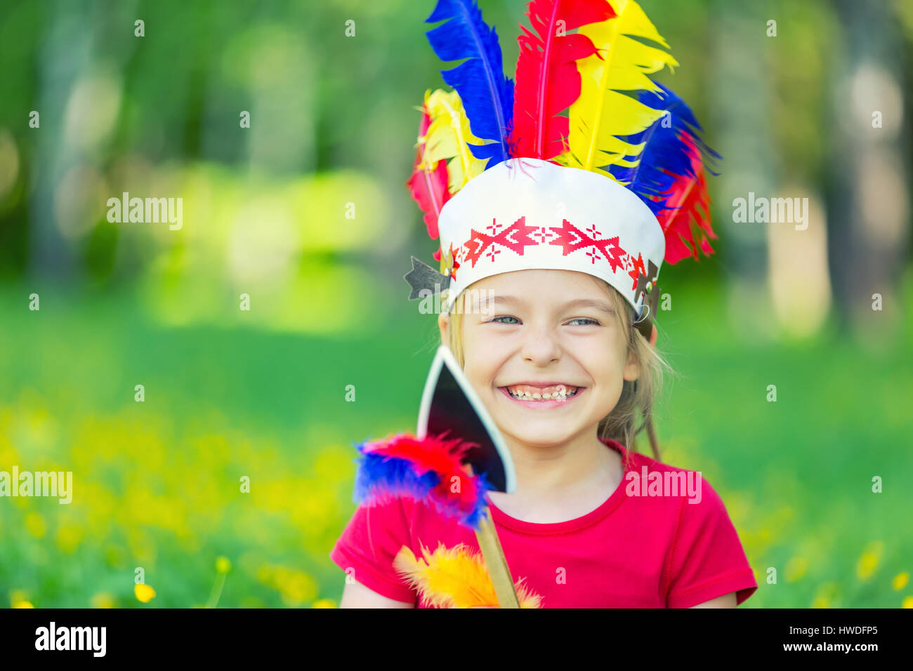 little funny girl playing native american - Stock Image