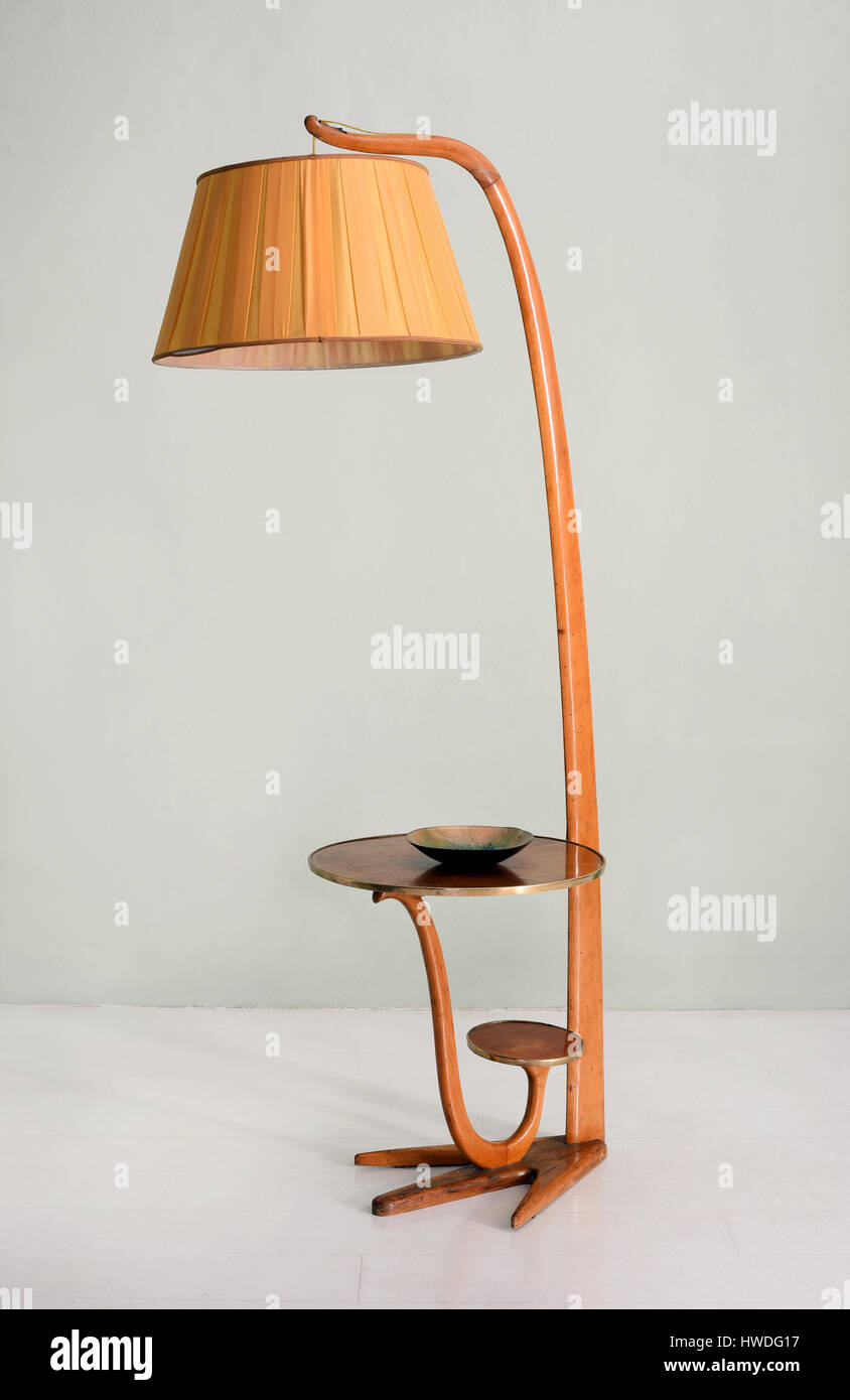 Still life of retro floor lamp with hanging shade and integrated still life of retro floor lamp with hanging shade and integrated table with small decorative bowl in room with plain background aloadofball Images