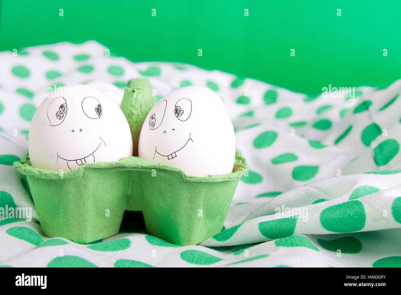 Easter eggs with funny faces in the green box on polka dot Stock
