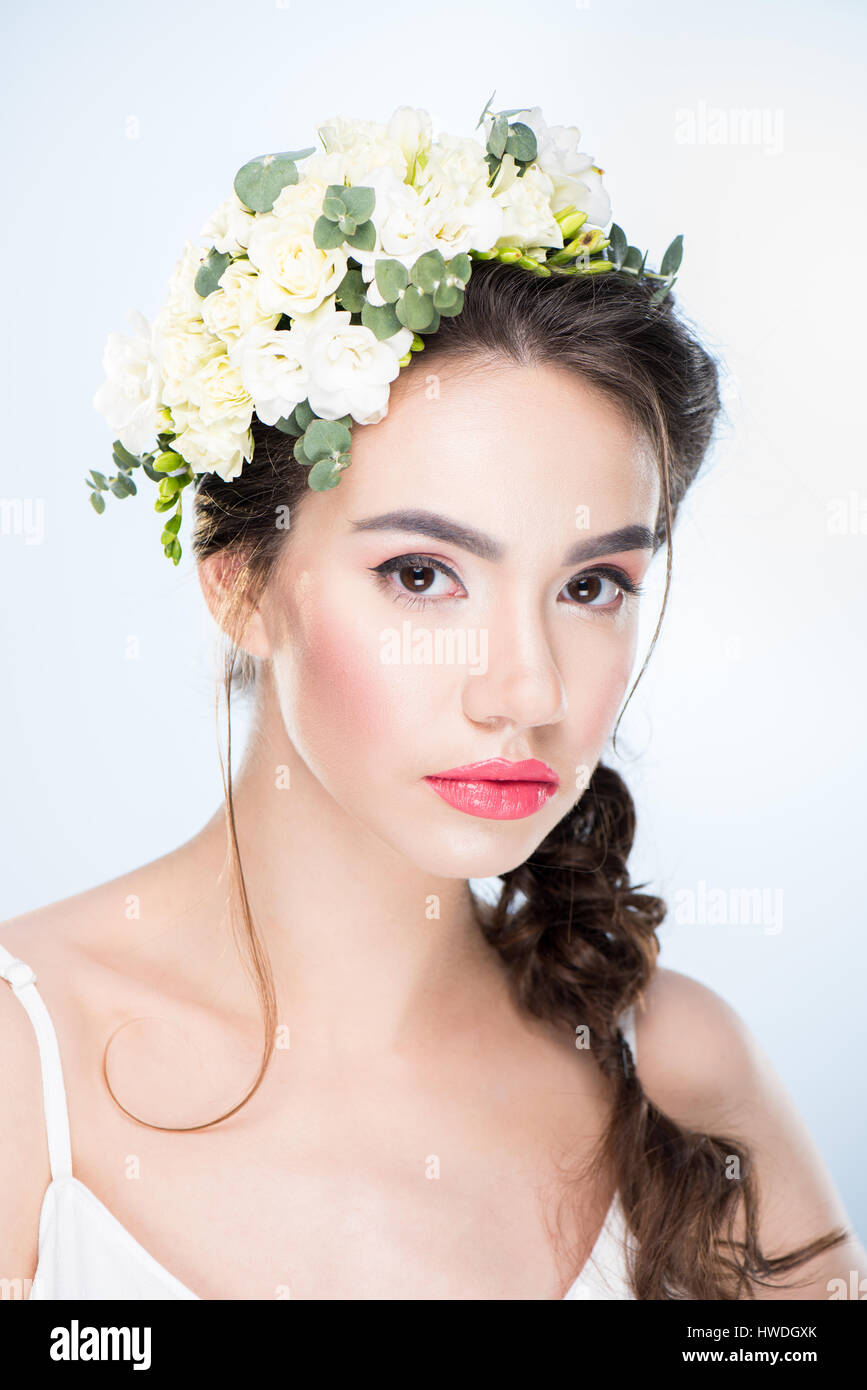portrait of serious woman with flowers in hair on white Stock Photo