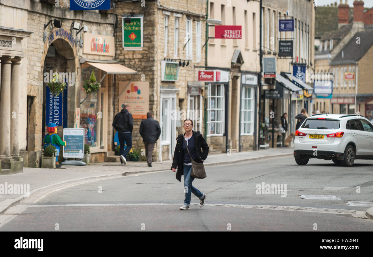 Woman walks across Market Place, Cirencester in the Cotswolds, Gloucester, England, UK Stock Photo