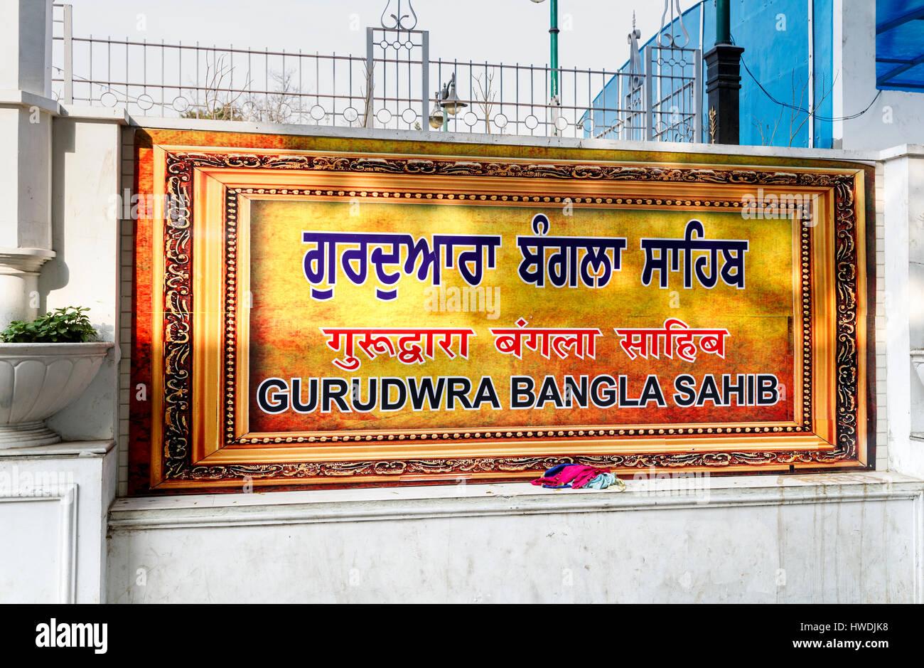 Colourful golden name sign at the entrance of Gurudwara Bangla Sahib, a Sikh temple in New Delhi, capital city of Stock Photo