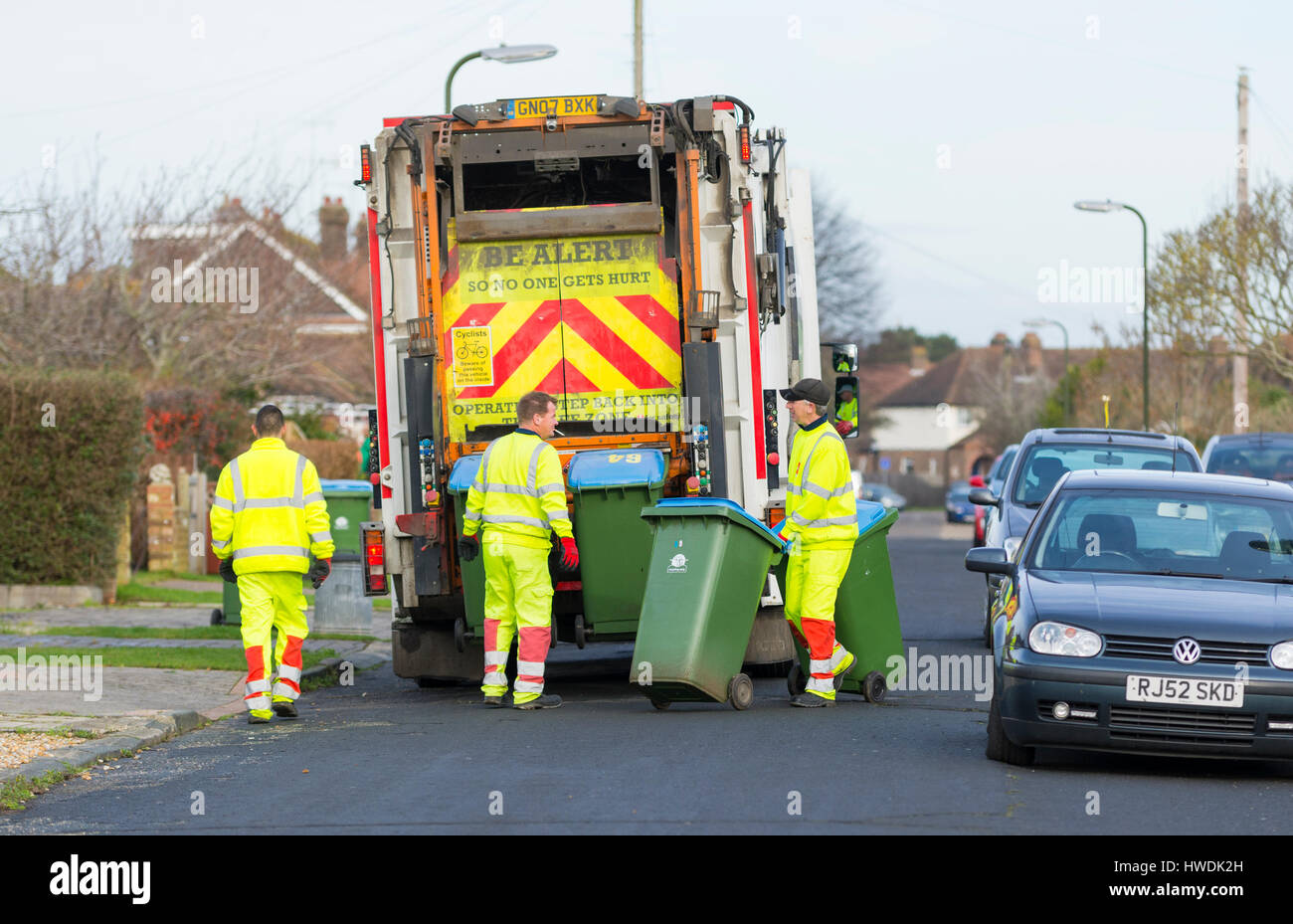 Several dustmen with a dustcart collecting rubbish on bin day in the South of England, UK. - Stock Image
