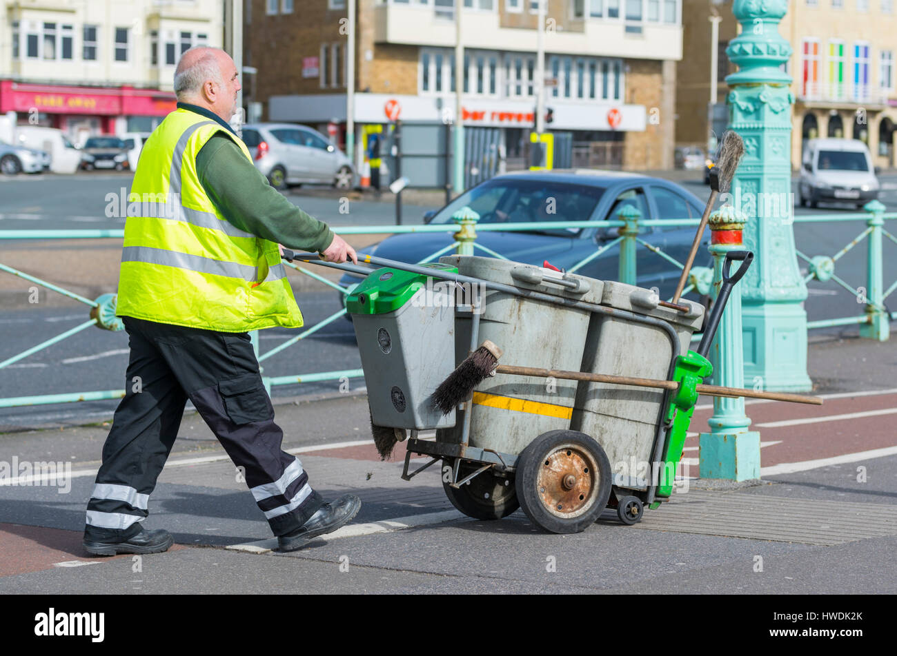 Male council street cleaner pushing a little bin in Brighton, East Sussex, England, UK. - Stock Image