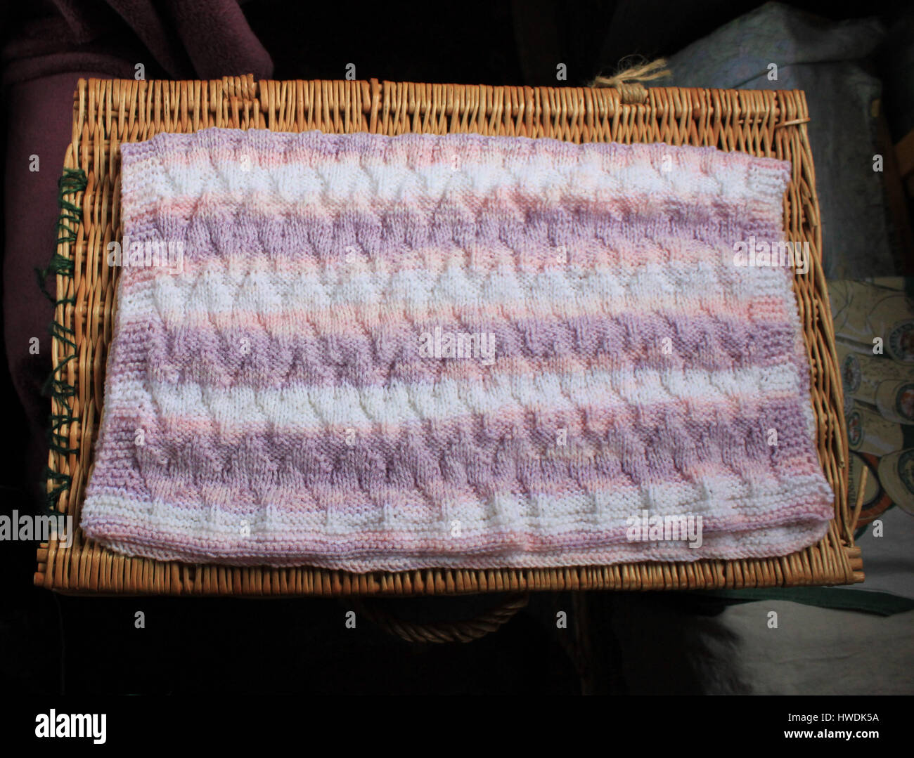 A lovely soft hand knitted baby blanket in colours of pastel shades of pinks, lilac, through to whites. The blanket - Stock Image