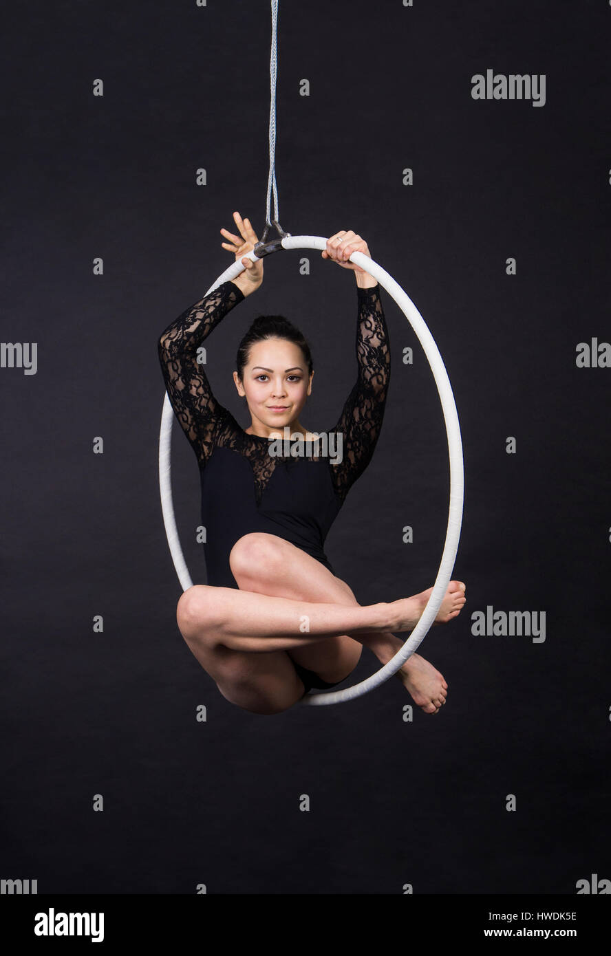 Aerial acrobat in the ring. A young girl performs the acrobatic elements in the air ring. Studio shooting performances - Stock Image