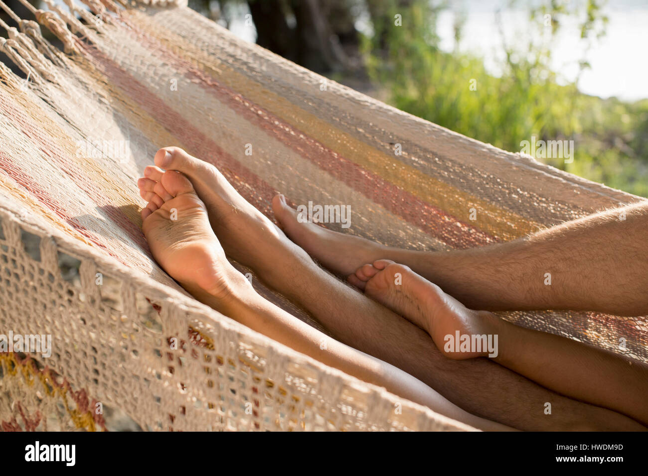 Couple relaxing in hammock, view of legs - Stock Image