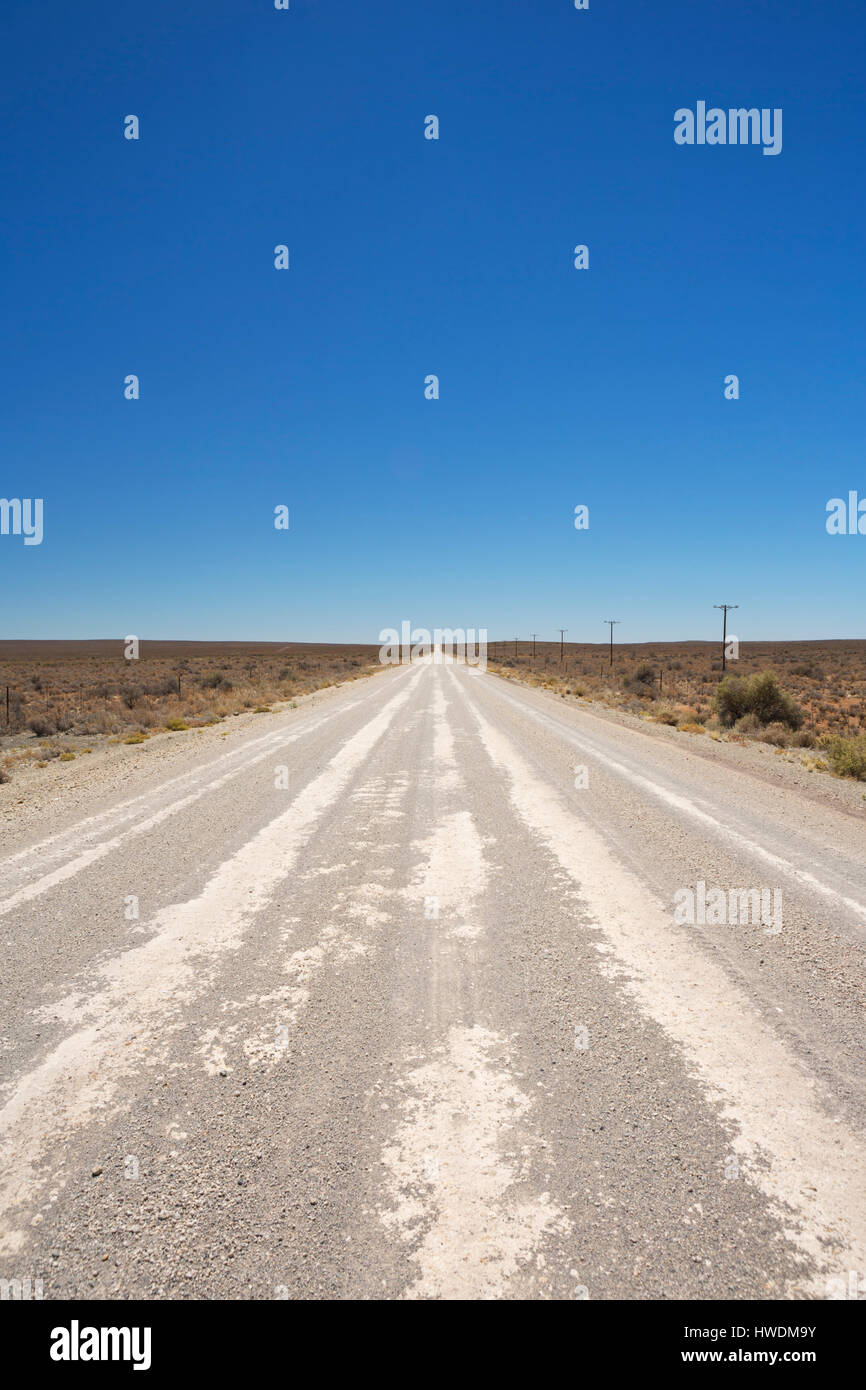 A straight dirt road through the dry Karoo semi-desert in South Africa. - Stock Image