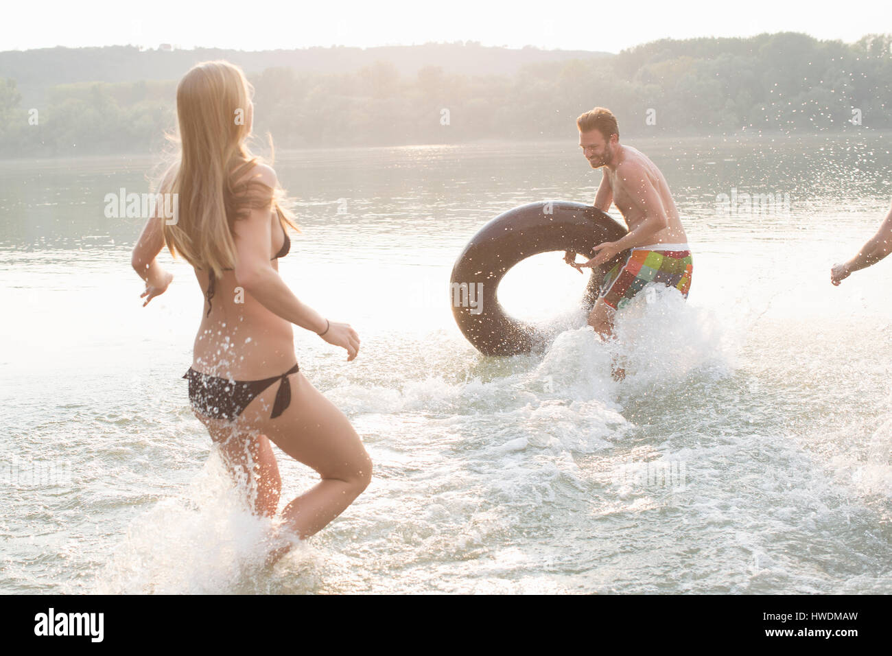 Friends having fun with inflatable ring in river - Stock Image