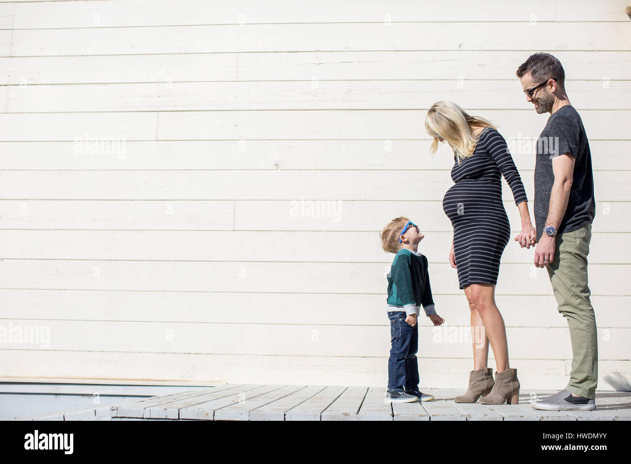 Parents and boy beside wooden building - Stock Image