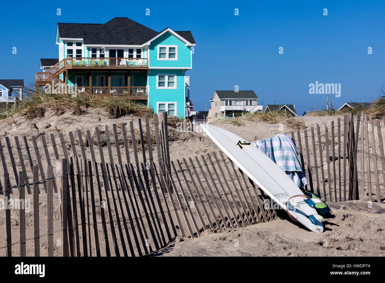 NC00746-00...NORTH CAROLINA - Surfboard, sand fence and beach houses at Rodanthe on the Outer Banks, Cape Hatteras Stock Photo