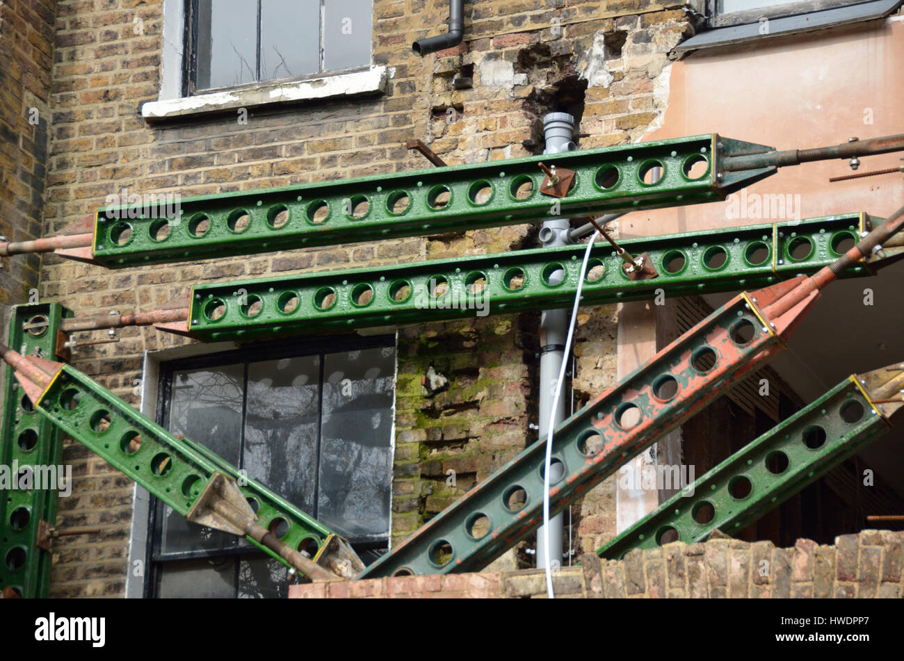 Iron girders supporting an unsafe residential building. Stock Photo