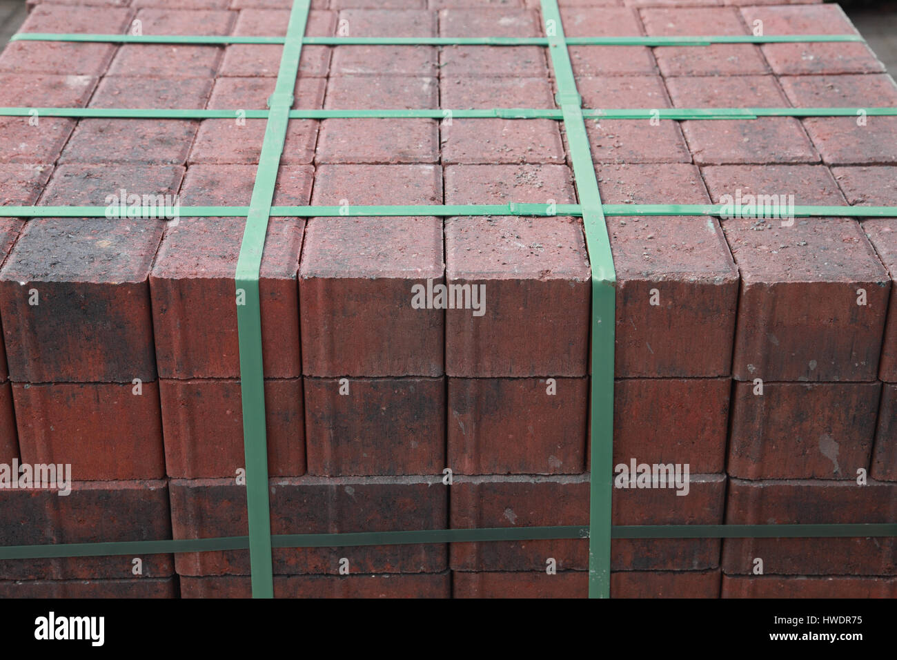 Pallet of newly delivered red bricks tied together with green tape - Stock Image