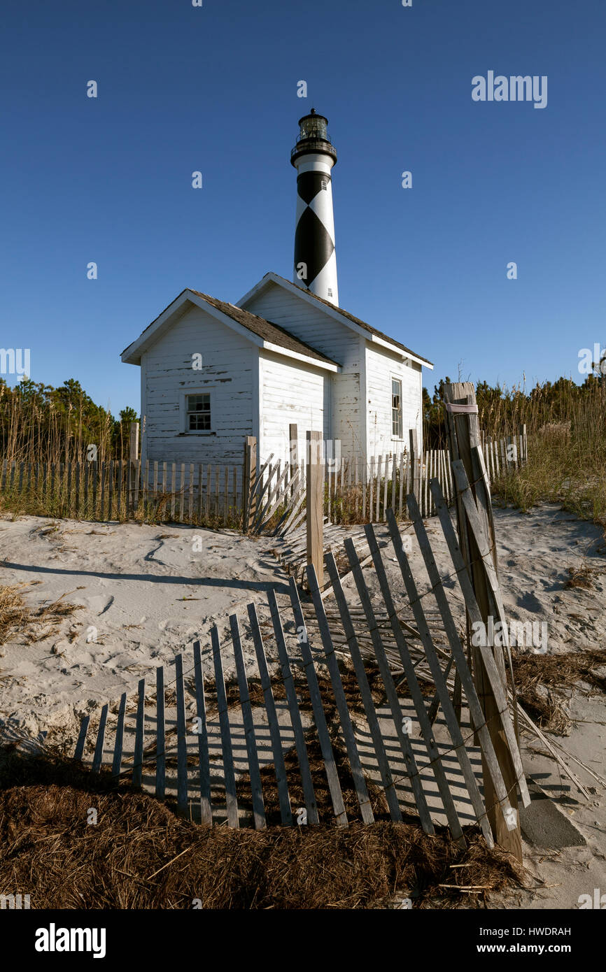 NC00878-00....NORTH CAROLINA -Sand fence, storage shed and Cape Lookout Lighthouse on the South Core Banks in Cape - Stock Image