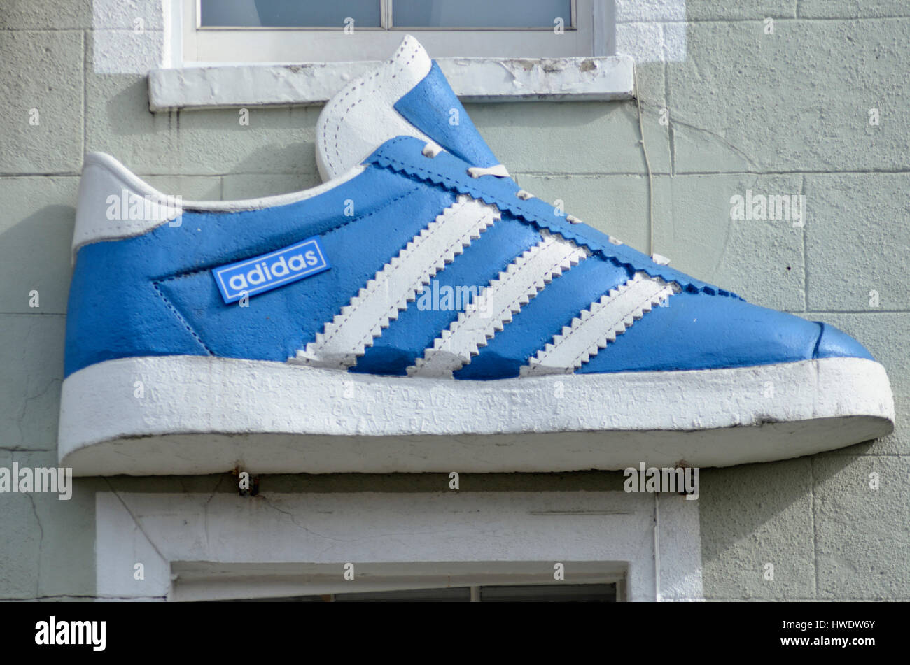 Giant Adidas training shoe on a shop building exterior. - Stock Image