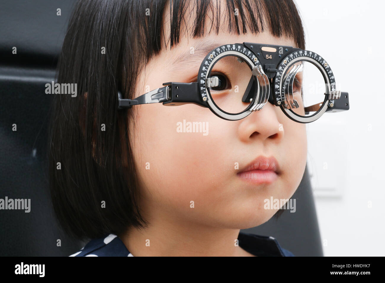 Asian Little Chinese Girl Doing Eyes Examination in isolated White Background - Stock Image