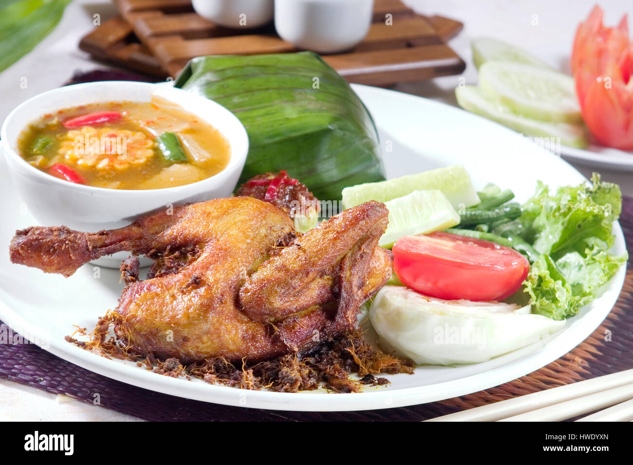 Ayam goreng Fried chicken Food Indonesia, serve with tamarind dish, sayur asam and rice - Stock Image