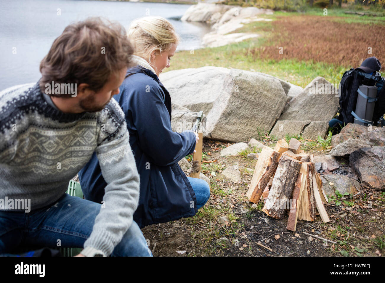 Man Looking At Woman Chopping Wood On Campsite - Stock Image