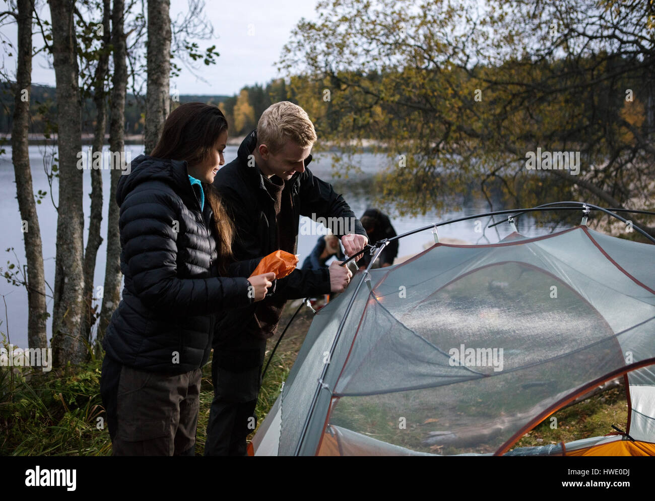 Young Couple Setting Up Tent By Lake - Stock Image
