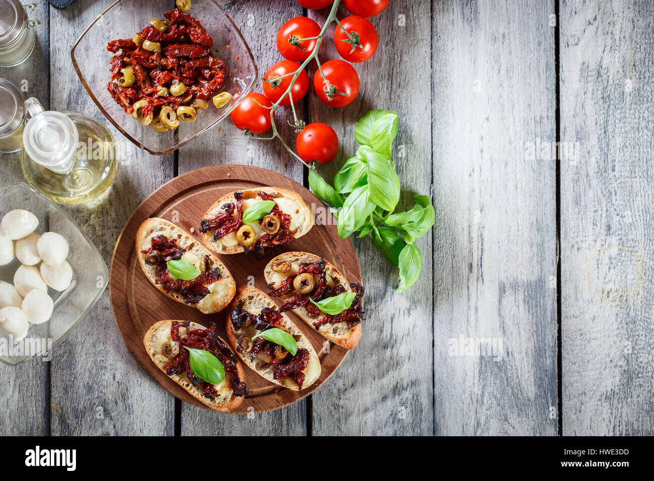 Appetizer bruschetta with sun-dried tomatoes, olives and mozarella. Italian cuisine. Top view - Stock Image