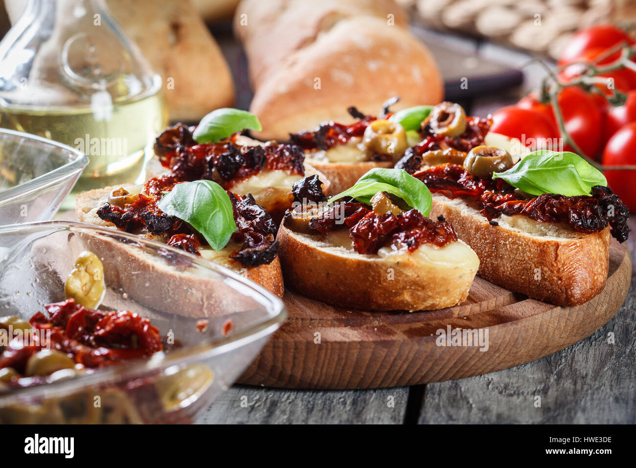 Appetizer bruschetta with sun-dried tomatoes, olives and mozarella. Italian cuisine - Stock Image