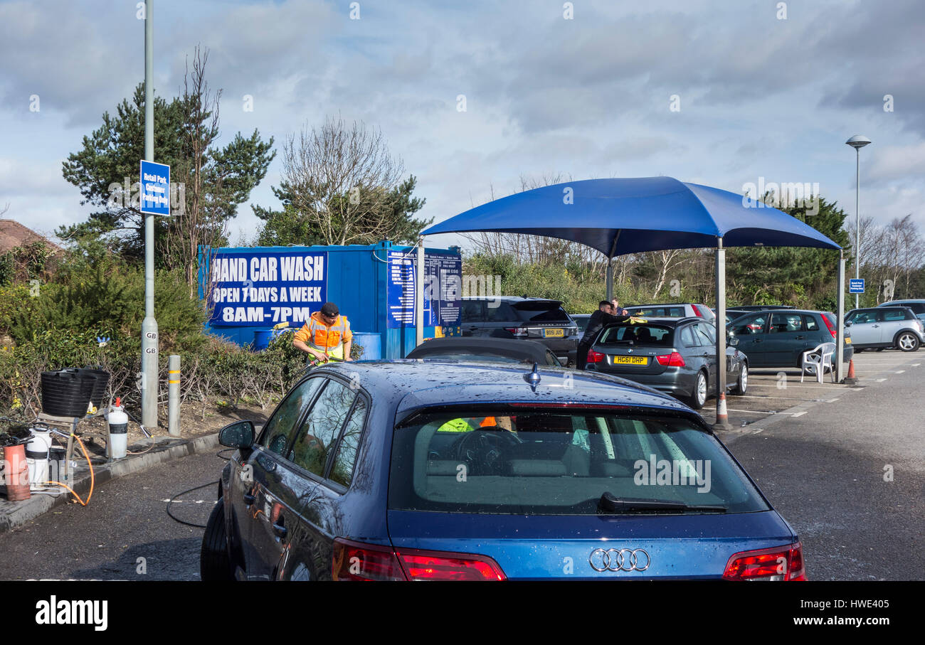 Cars Being cleaned at a Hand Car Wash  Unit in a Car Park in Poole, Dorset, UK - Stock Image