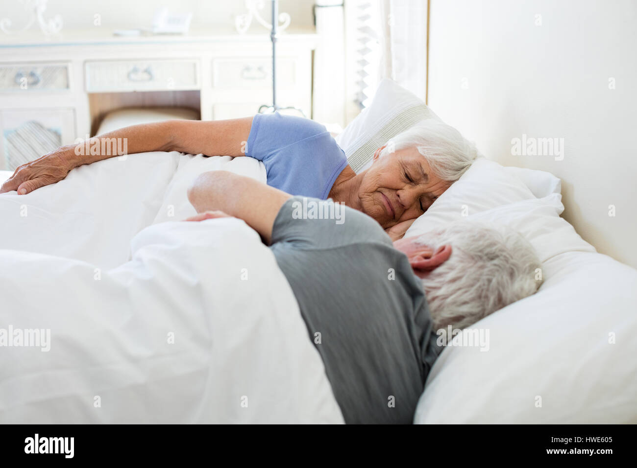 Senior couple sleeping in the bedroom at home - Stock Image