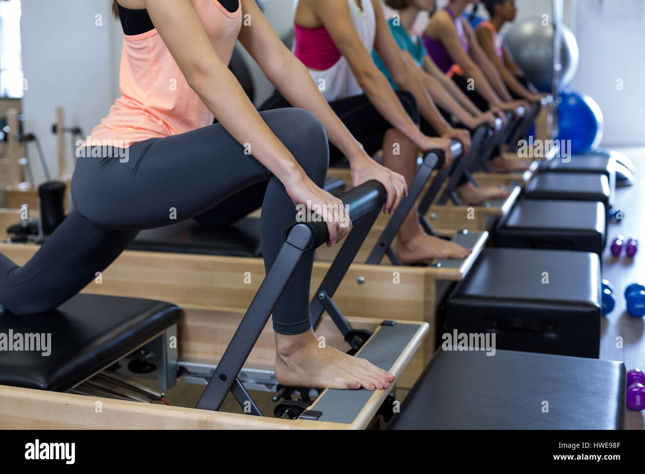 Group of women exercising on reformer in gym - Stock Image