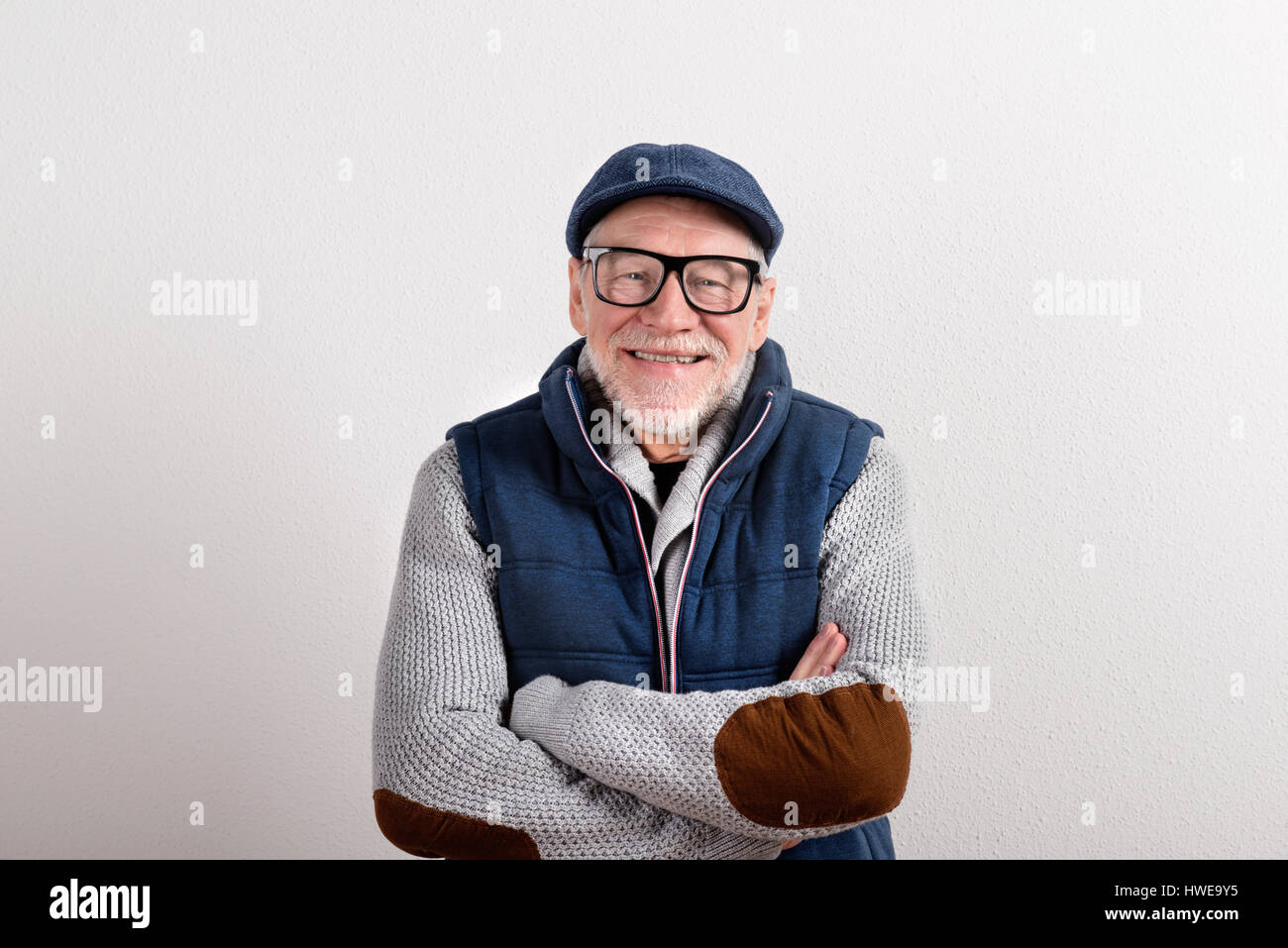 Senior man in sweater, vest jacket and cap, studio shot. - Stock Image