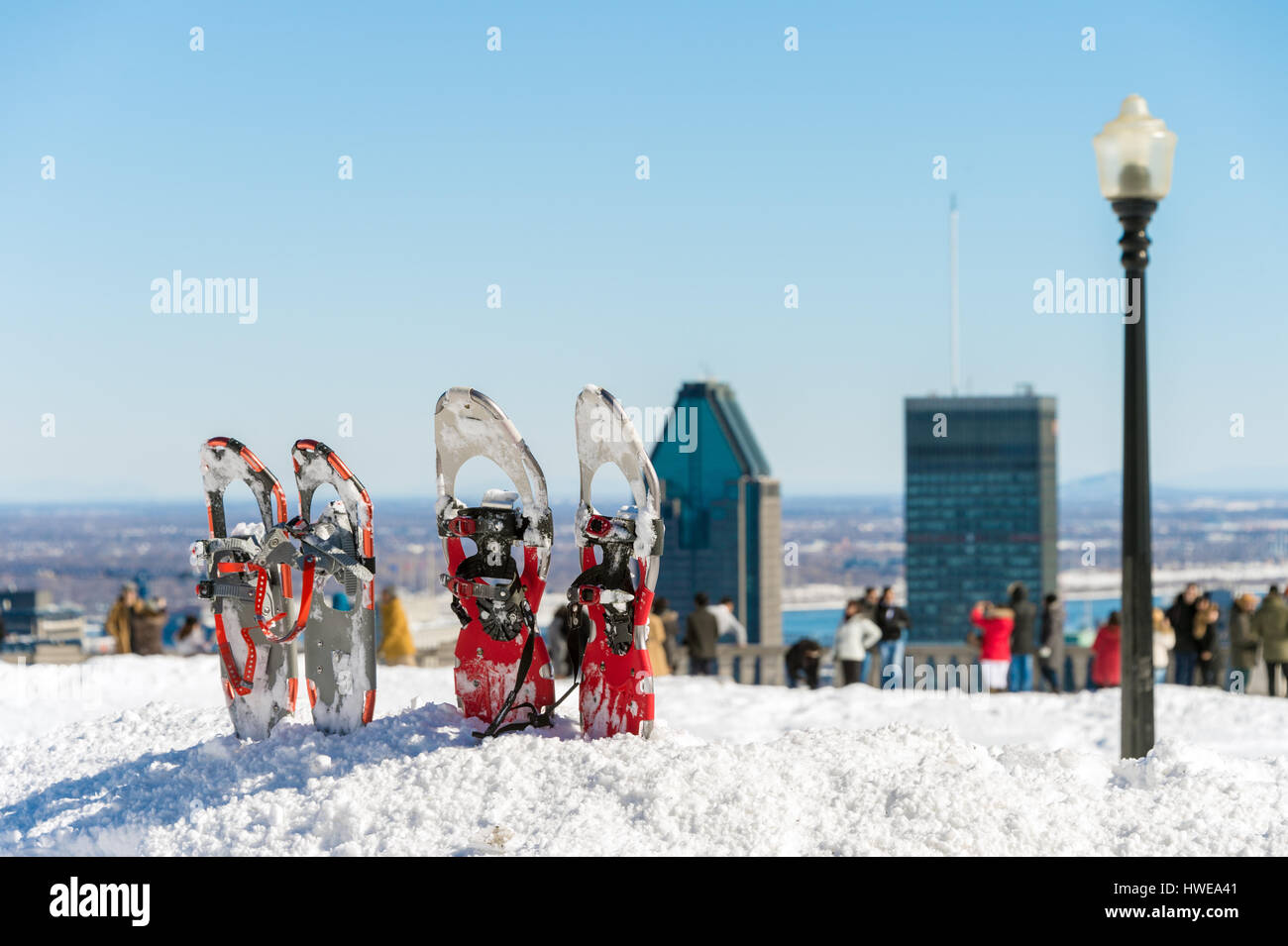 Snowshoes in snow with Montreal skyline in the distance - Stock Image
