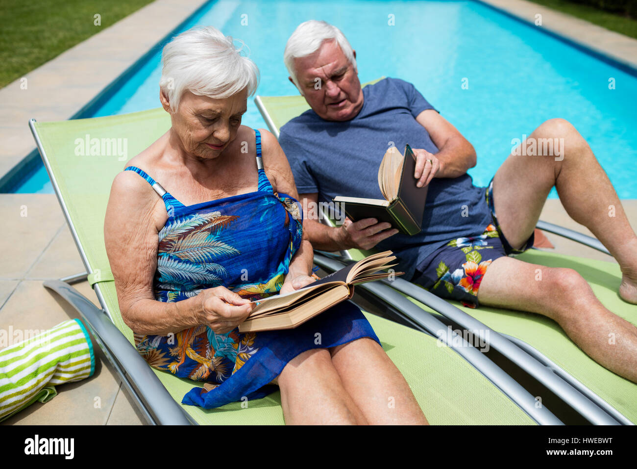 Senior Couple Reading Books On Lounge Chair At Poolside   Stock Image